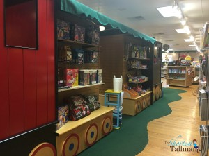 Inside The Village Toy Shop, there is a giant train that serves as display shelves and play space for kids!
